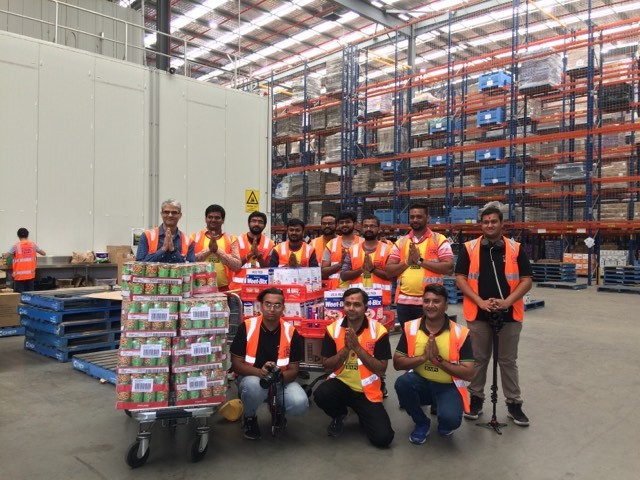 One of the many community groups who visited the warehouse to make a generous food donation for the bushfire appeal. The shelves in the background give you a small sense of just how massive Foodbank's operations are. Foodbank NSW/ACT Warehouse, Glendenning NSW, January 2020. (Image supplied by Kathleen Notohamiprodjo).
