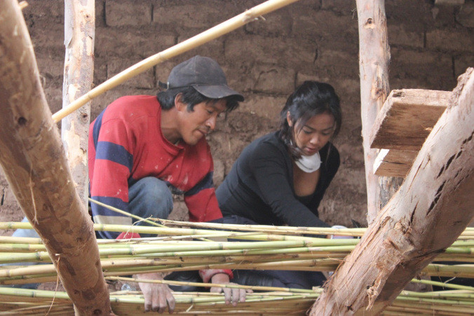 Criselda helping to nail down bamboo on the roof rafters