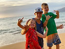 Fit man with young daughter and young son standing on a beach in Maui making hang loose signs with their hands