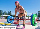 fit woman competing in weightlifting at an outdoor stadium