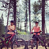 Two women standing in the forest in front of mountain bikes