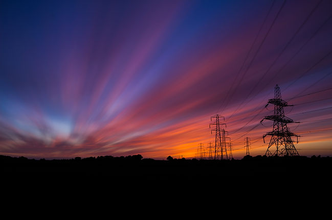 Electric lines in the sunset. Energy power lines supported by natural gas from shale