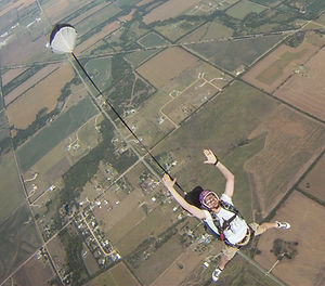 Aaron jumping out of an airplane with a parachute.