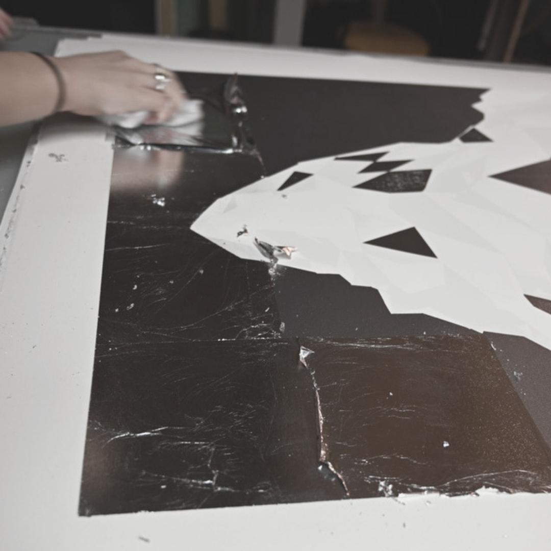 Hand applying silver leaf