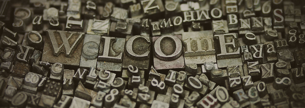 """Printing press letter tiles spelling out """"Welcome"""""""
