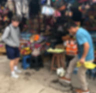 Connecting through soccer. Peruvian market juggling soccer ball with new friends