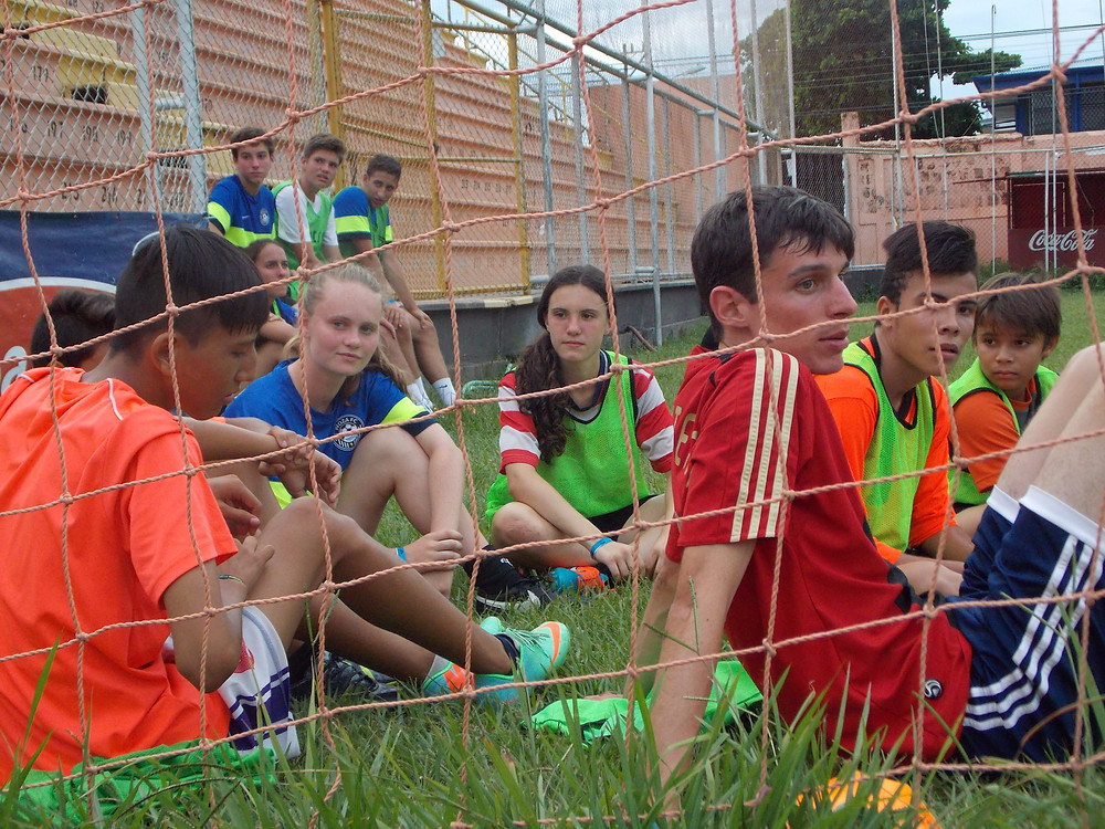 A group of soccer players from different cultures coming together to bond on the sideline of the soccer field.