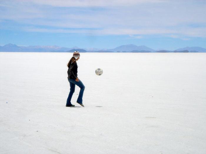 Woman juggling a soccer ball on an open landscape.