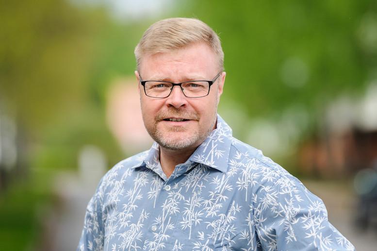 vaaleahiuksinen mies ulkona mustasankaiset silmälasit päässä