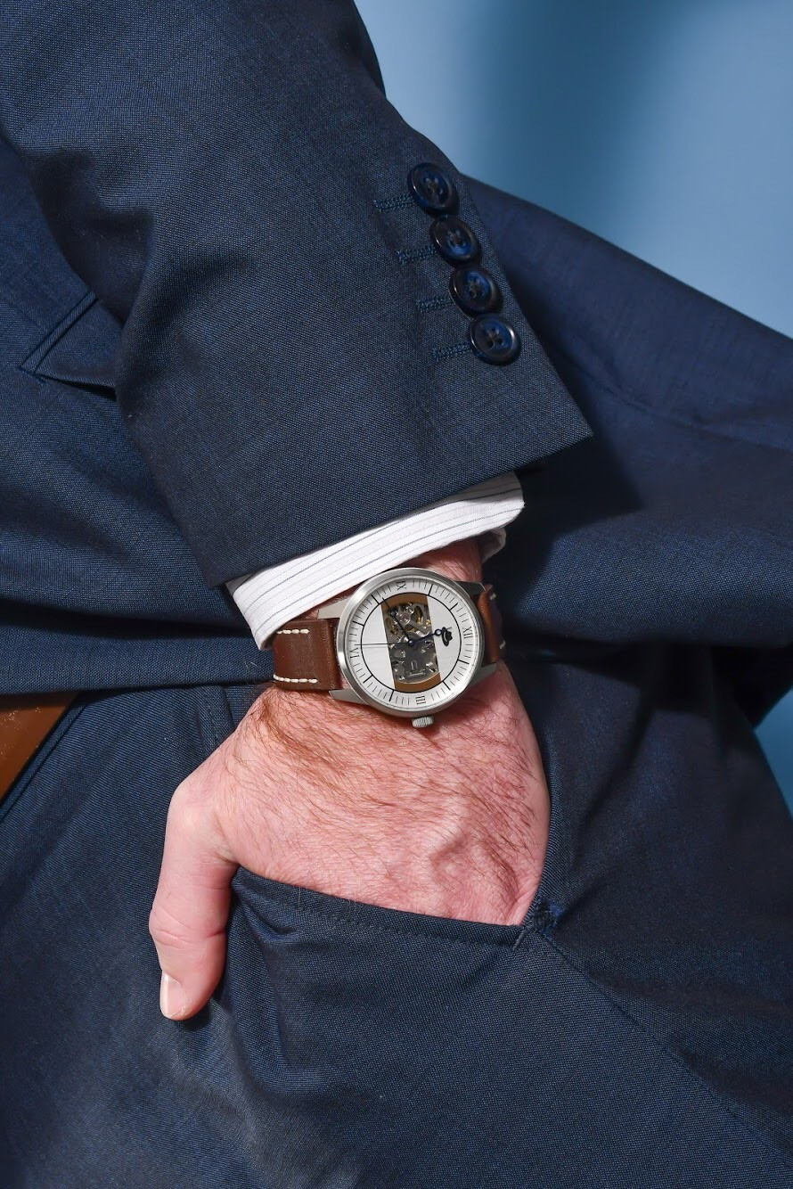 Man wearing suit with a luxury watch on his wrist.