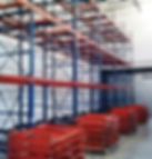 Installation of push back system, pallet racks, red rails laying in piles in warehouse