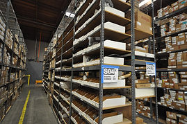 Shelving rackes installed in a warehouse, stacked with boxes, parts, and other equipment