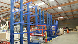 Cantilever racks Structural blue, installed in warehouse, scissor lift equipment standing next to it