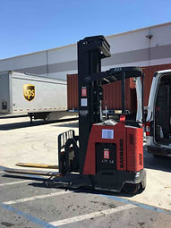 Raymond R45TT Stand Up Reach Forklift outside next to trucks and a building