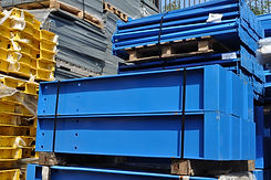 A lot of blue cantilever racks bases in a stack outside