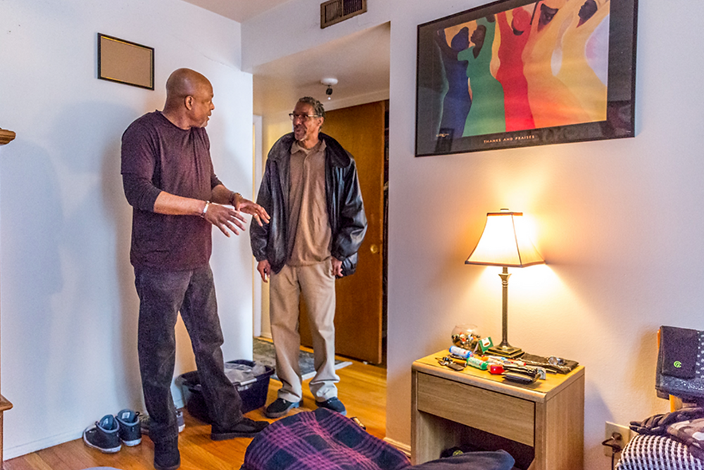 """Jerome Arnold, right, checked in with Marine veteran Ron Clark on March 12 at Clark's apartment. """"I keep everything tidy and in order,"""" Clark said. """"When I read the good book, God is a God of order, and I want to live that way."""" Photo Credits: Lisa Johnston 