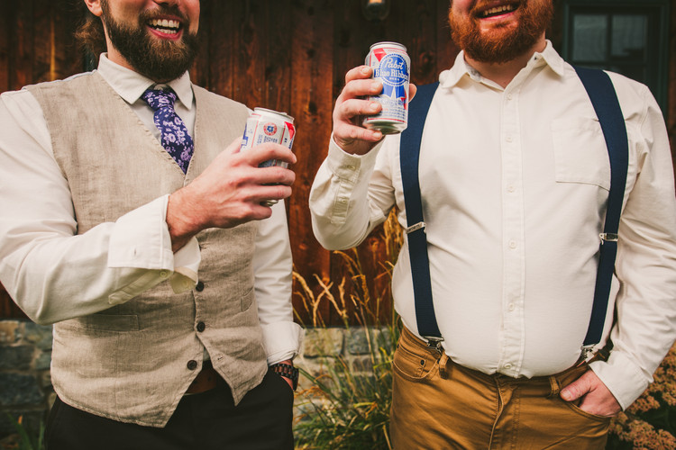 Groomsmen enjoy a beer before a hot summer wedding