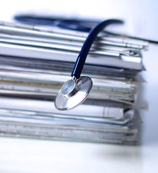 Medical stethoscope on the stack of pape