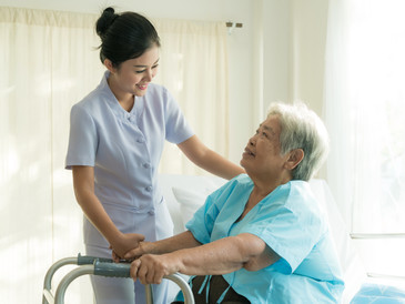 Young nurse supporting elderly patient