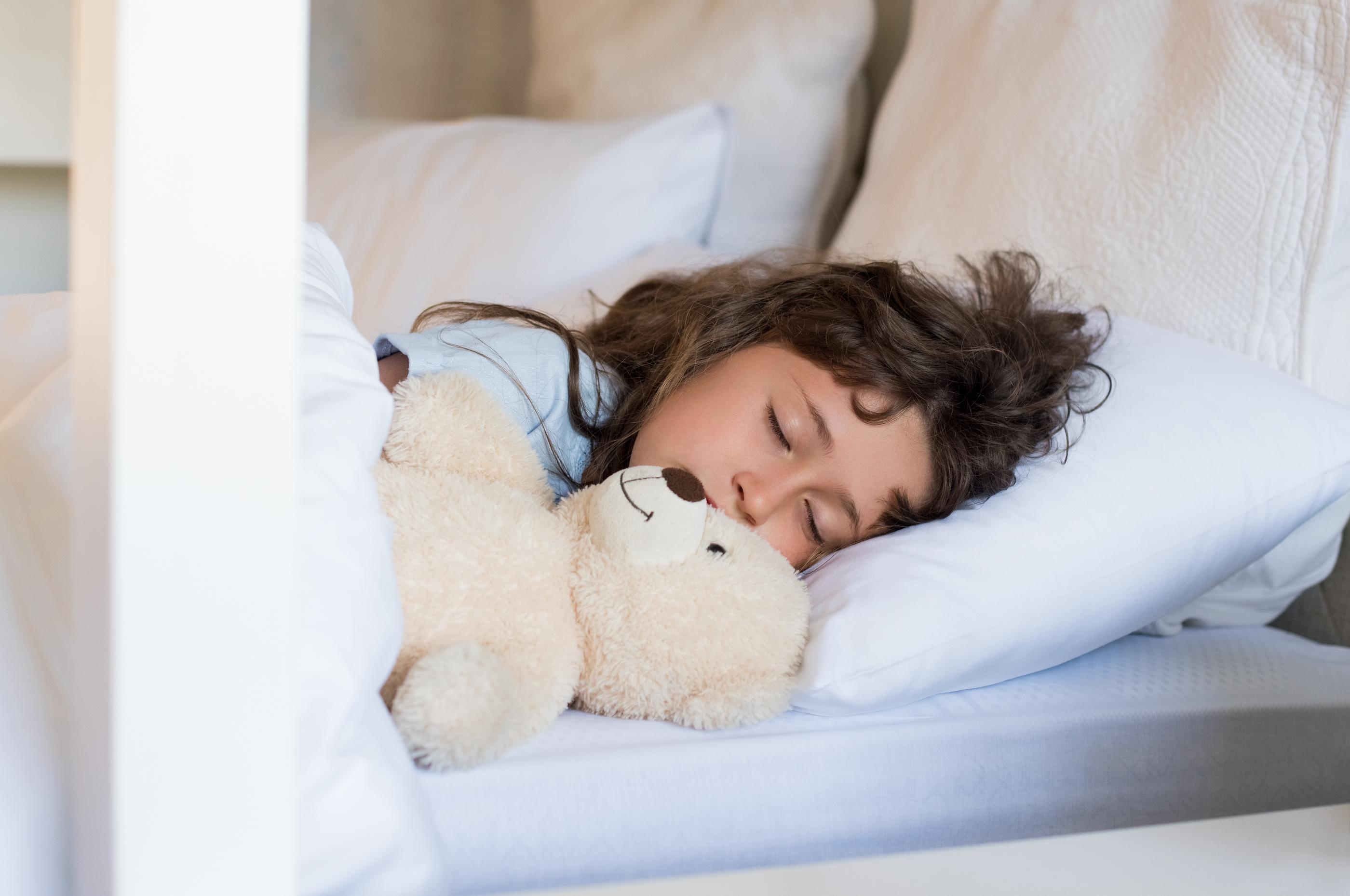 Sweet child sleeping in bed. Little girl sleeping with teddy bear at morning. Cute little girl sleep