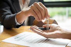 real estate agent holding house key to h