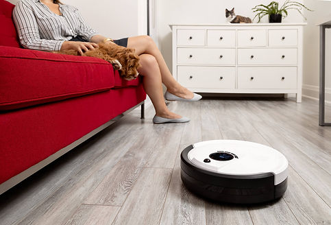 Owner and dog sit on couch while Junior vacuums the floor