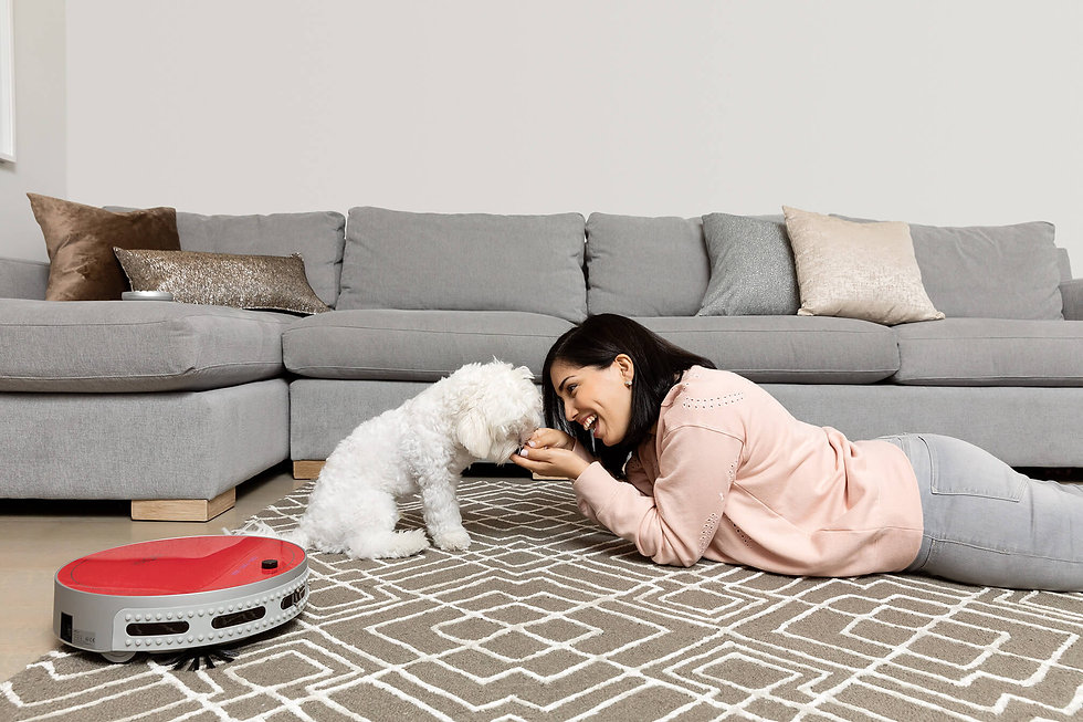 Girl and her dog playing while bObi Pet in scarlet vacuums the rug