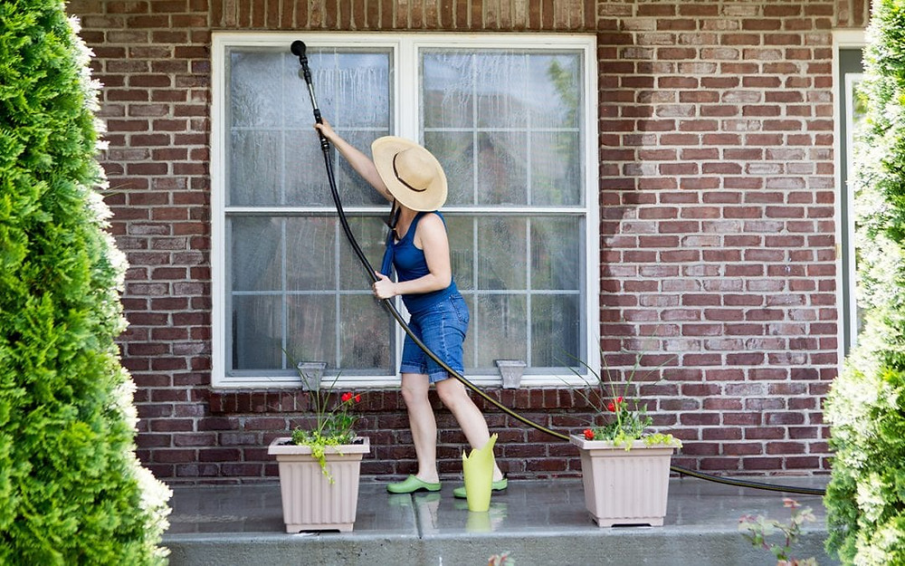 Woman cleaning outside windows with the sun out in summer