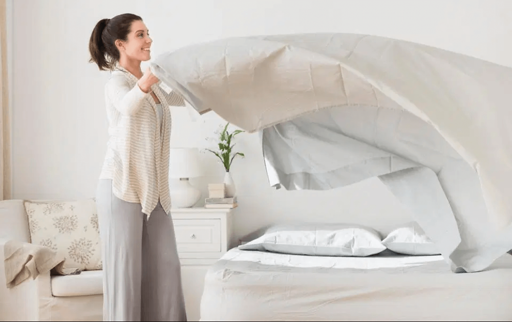 Woman fluffing her bedsheets and making the bed