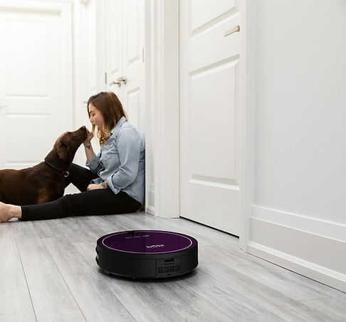 Girl playing with dog while bObi Classic in blackberry vacuums the hardwood floor