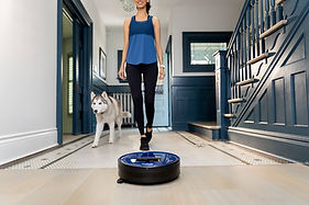 girl and her dog husky walk towards bob pethair plus robot vacuum in cobalt blue