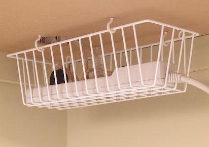 Power strip hidden in a hanging basket under the desk.