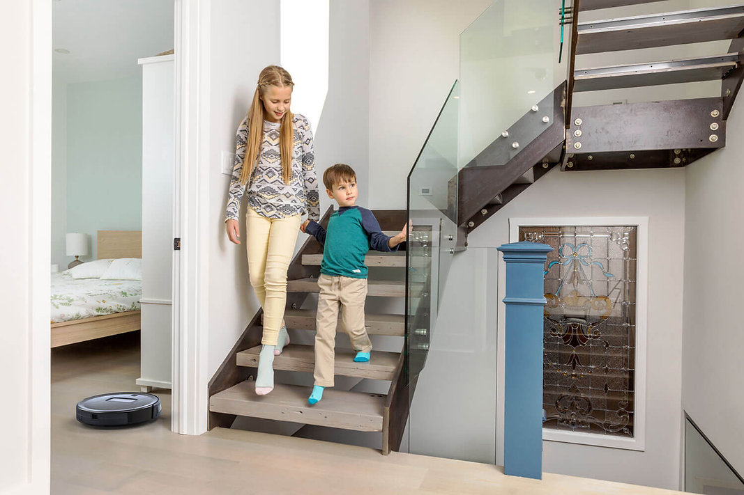 Girl and boy walk down stairs in home while Bob PetHair Vision vacuums the bedroom