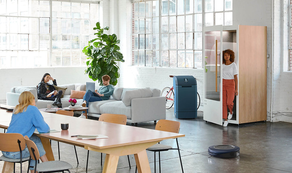 Work office with people hanging out with a smart bin and robotic vacuum cleaner