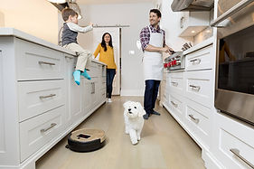 family gathering in kitchen with dog and bob standard robot vacuum in champagne gold