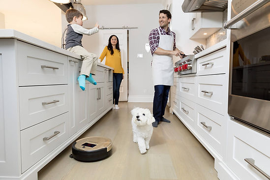 Family in kitchen with dog while Bob PetHair vacuums under the cabinets