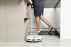 lady walks in kitchen while bobi classic robot vacuum cleans kitchen floor