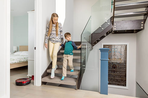 Kids walk down the stairs at home while Bob PetHair vacuums in the bedroom
