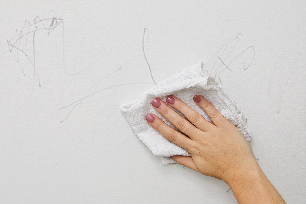 Wiping crayon marks off a white wall