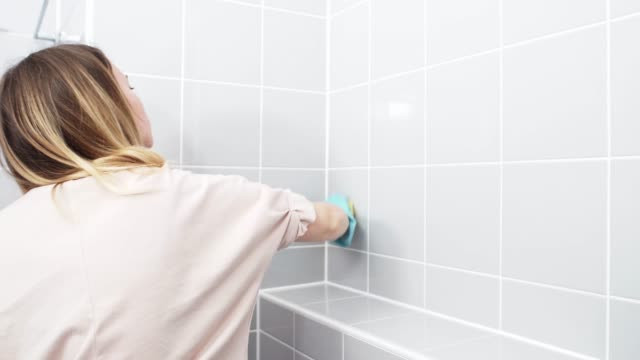 Girl cleaning mould and mildew off of shower wall