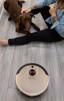 girl and her dog sitting on floor with bob standard robot vacuum in champagne gold