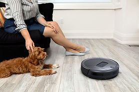 woman and her dog sitting on couch while bob pethair vision robot vacuum cleans