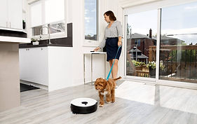 Woman and her dog walk into house while Junior robot vacuum cleans