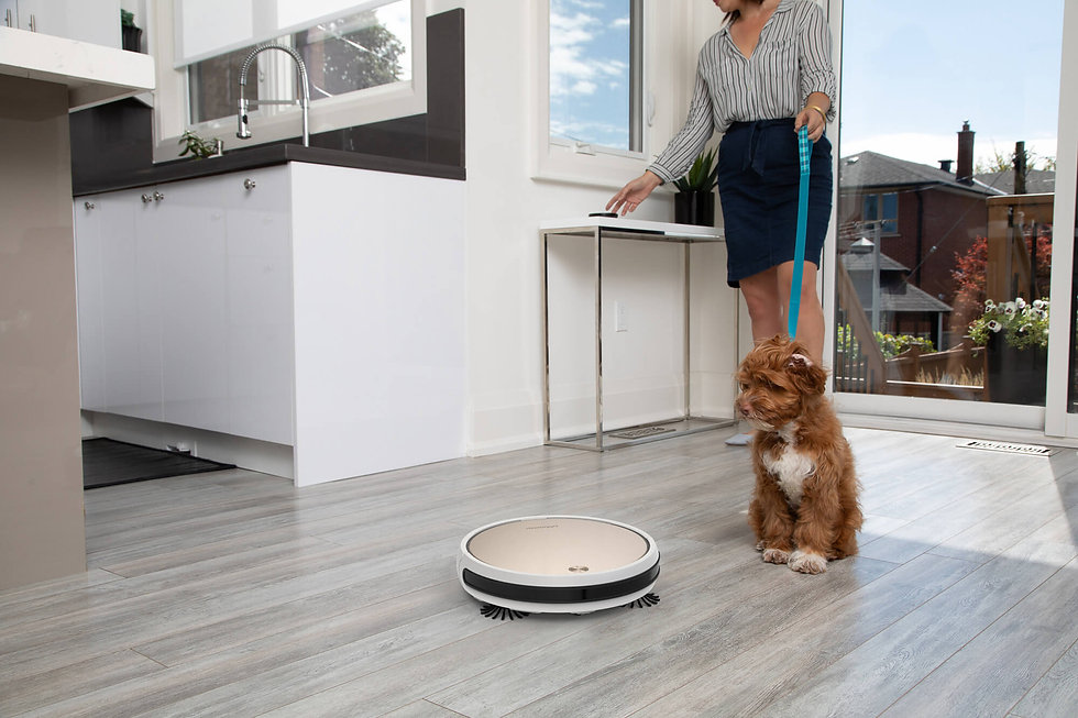 Woman reaching for remote control as Bob Pro vacuums the kitchen floors