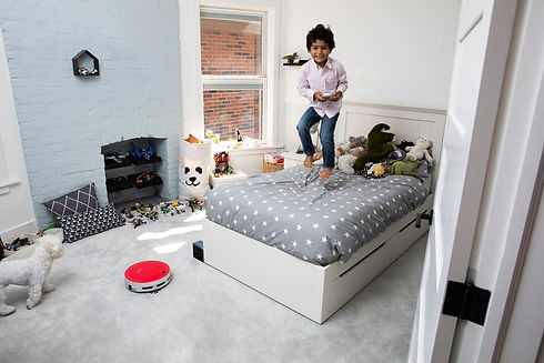 Little boy jumping on bed while using the bObi remote control to tell bObi pet to clean his room