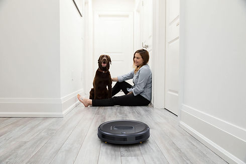 Girl and dog sitting in hallway while Bob PetHair vacuums the floor