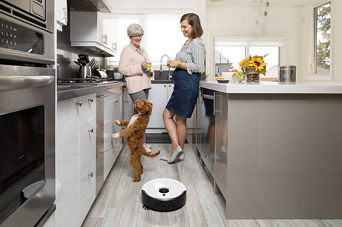 Two ladies chatting in the kitchen while dog plays and Junior sweeps the floor