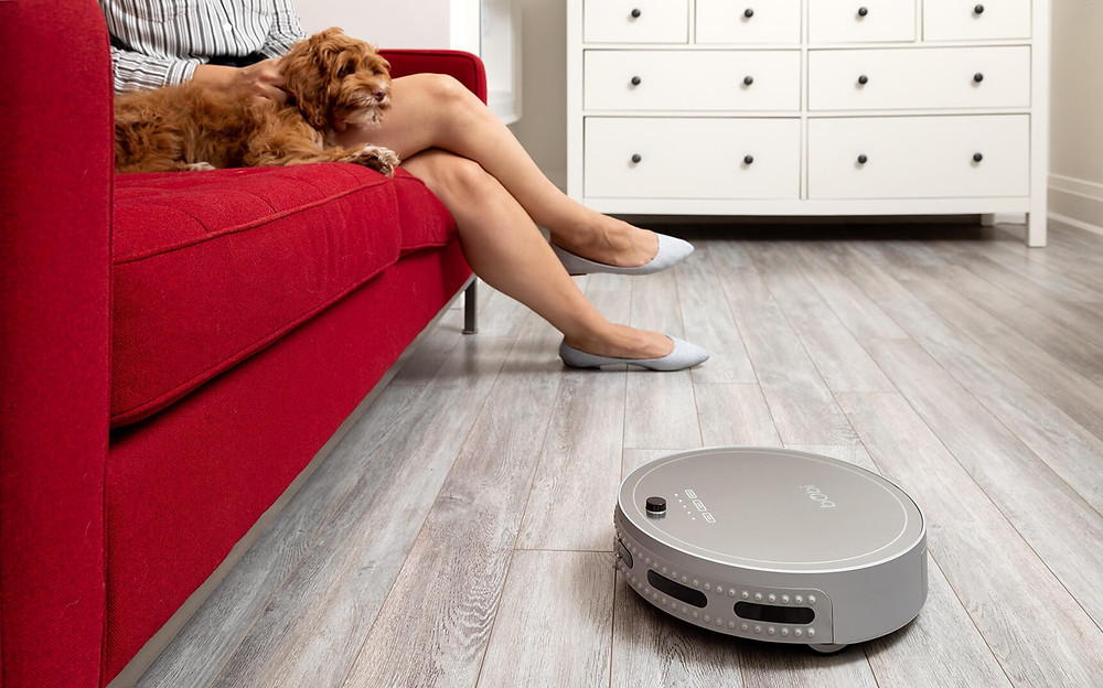 Lady and dog sitting on couch with bObi Pet robot vacuum sweeping the floor underneath