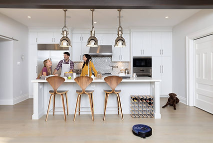 Family in kitchen while Bob robot vacuum sweeps