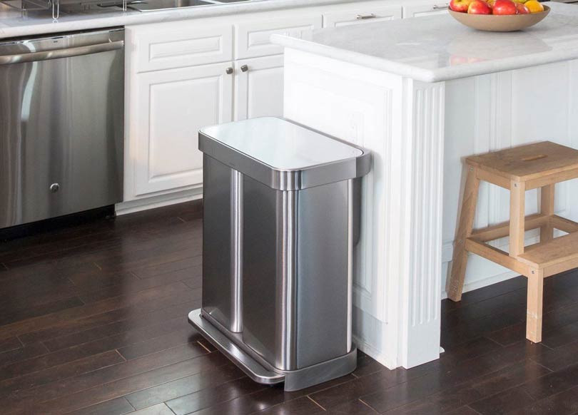Cleaning silver garbage bin sitting by kitchen island